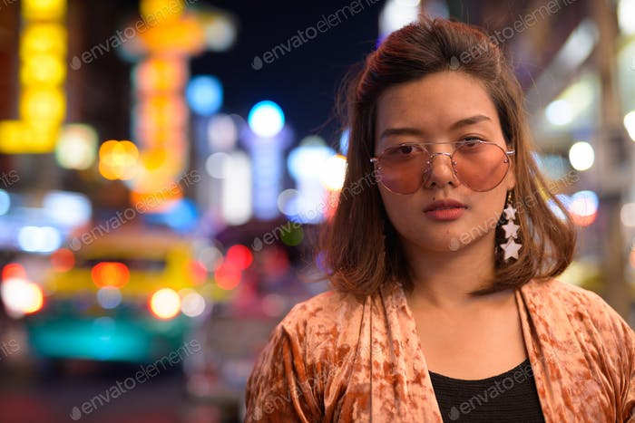 Face of young beautiful Asian tourist woman at Chinatown in Bangkok