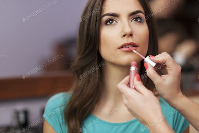 Applying lip-gloss to the lips of beautiful woman