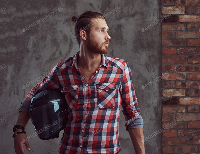 Handsome redhead biker in a flannel shirt, holds motorcycle helmet, posing on a gray background.