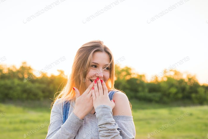 Surprised young woman covering her mouth with hands outdoors
