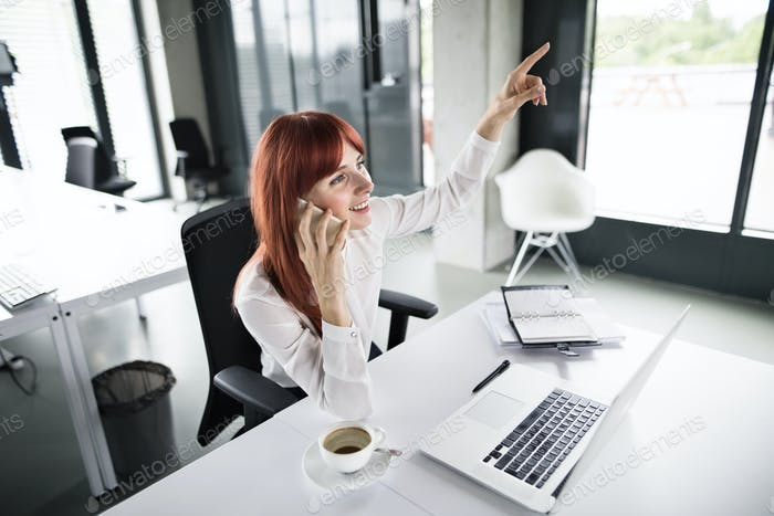 Businesswoman with smartphone and laptop in her office.