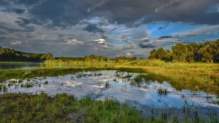 Cloudy sky over beautiful flood plain landscape
