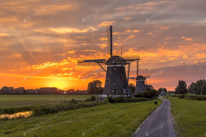 Wooden windmills at orange sunset