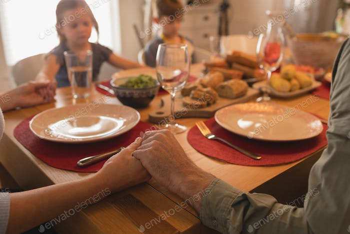 Close up of family praying before having food on dining table at home