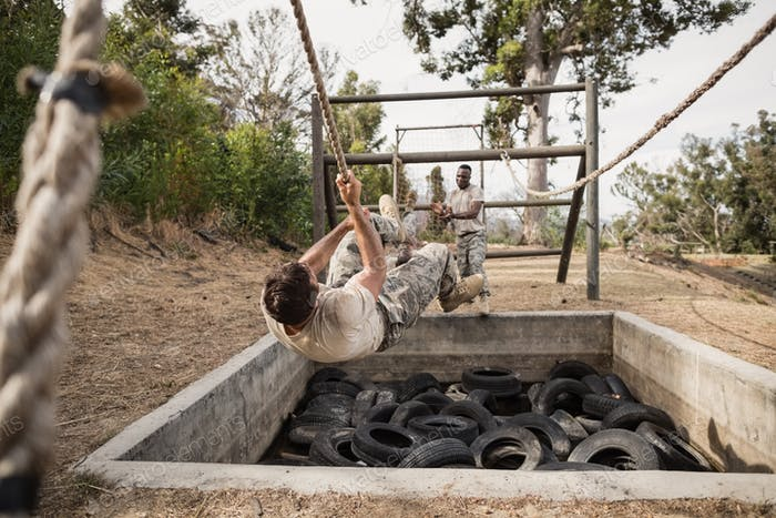 Young military soldiers practicing rope climbing during obstacle course