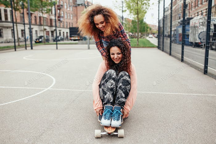 Young girls skating in basketball court