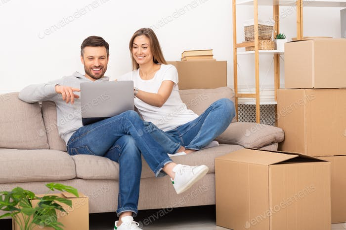 Young couple sit in new apartment with laptop, discuss home repair project