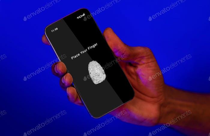 Black man holding phone with fingerprint scanning app