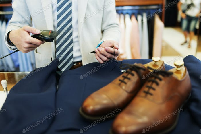 Midsection of sales clerk using bar code reader on suit in clothing store