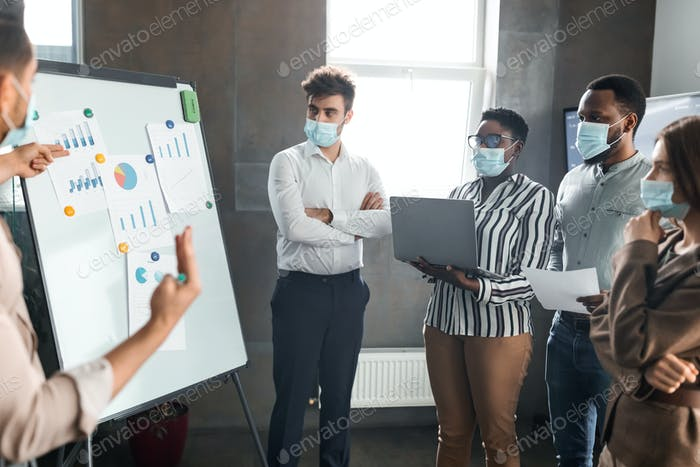 Employee in protective mask presenting business strategy on whiteboard