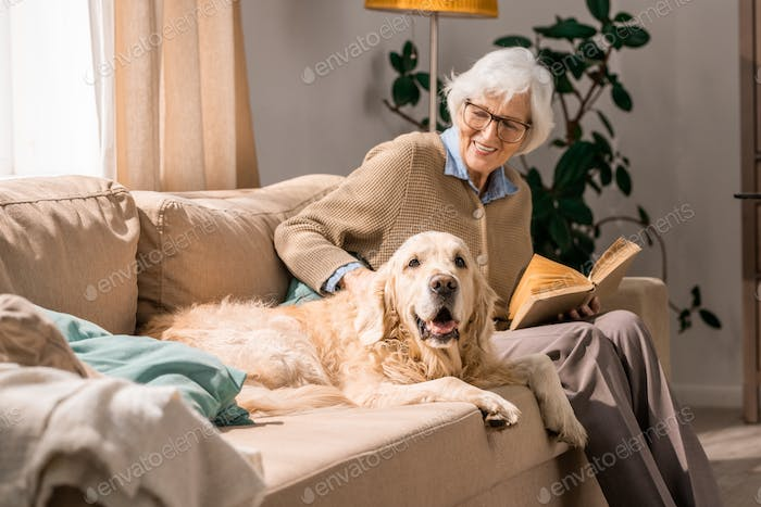 Happy Senior Woman  Cuddling with Dog on Couch