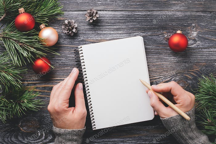 Woman's Hand Writting in Notebook and Christmas Decorations.