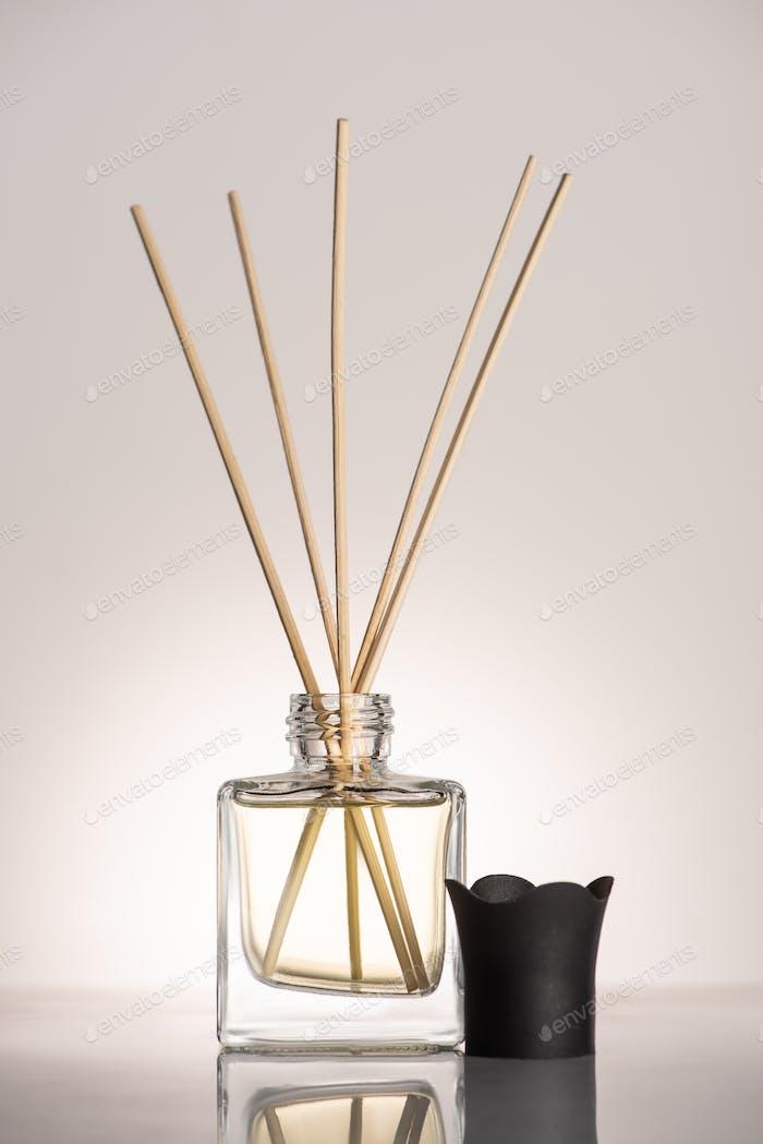 Wooden Sticks in Perfume in Bottle on Beige Background