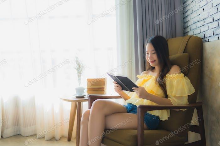 Retrato joven mujer asiática sentarse en sofá silla y leer libro con taza de café
