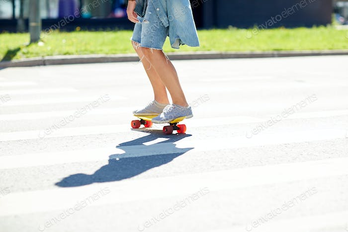 teenage boy on skateboard crossing city crosswalk