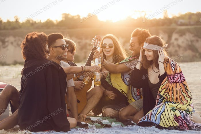 Group of happy young people sitting together at the beach