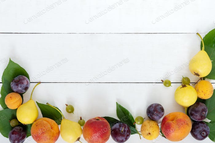 Fresh fruits on a white wooden background. Copy space.