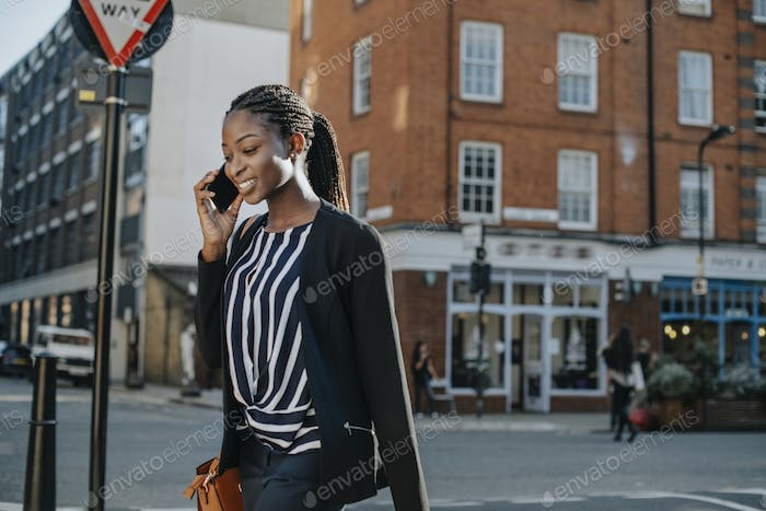 Woman on the phone while walking in the city