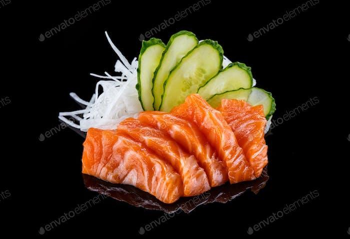 Salmon sashimi over black background