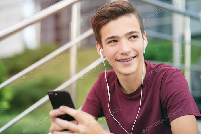A smiling young man with a smartphone, in the street.