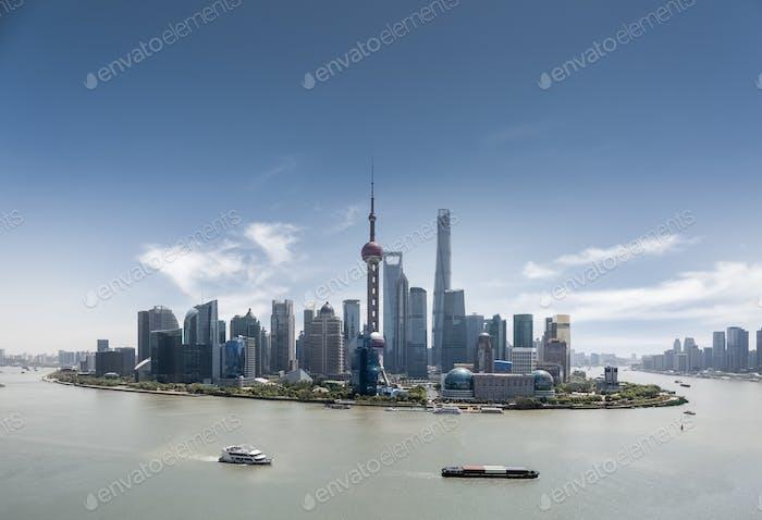 shanghai skyline against a blue sky in daytime
