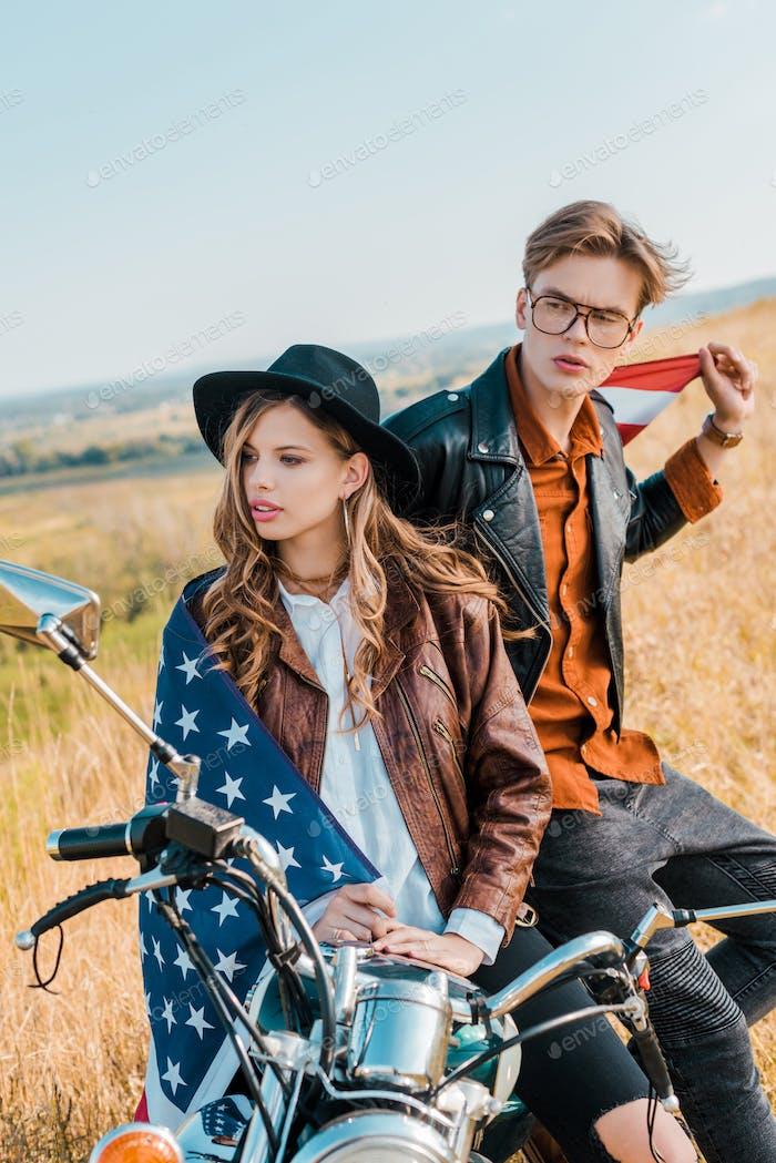 Junges Paar mit amerikanischer Flagge sitzt auf Motorrad, Unabhängigkeitstag Konzept
