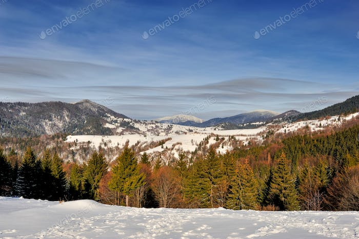Nice mountains view in snowy sunny day under blue sky with sun l