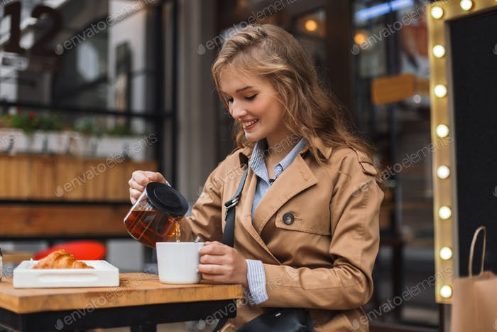 Young woman in trench coat happily holding teapot and white cup