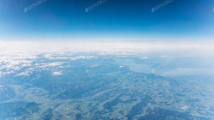 Draufsicht auf Berge mit Schnee und Wolken. Blick auf die Alpen.