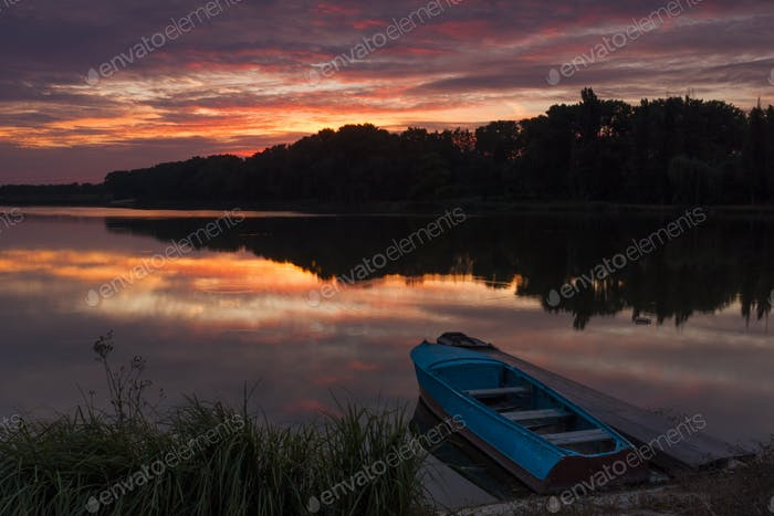 Boat near the shore of the lake at sunset