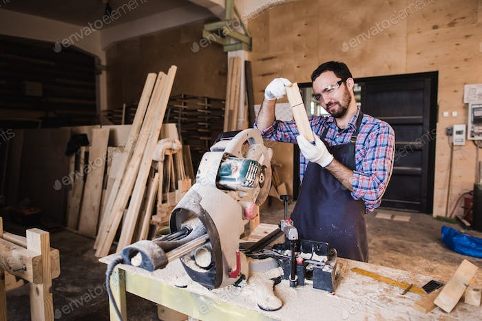 Carpenter working on an electric buzz saw cutting some boards, he is wearing safety glasses