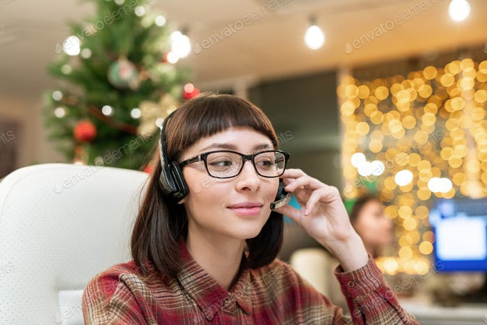 Pretty young female operator with headset consulting clients on Christmas day