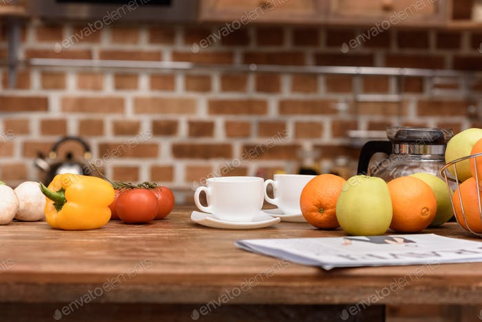 cups with coffee and vegetables with fruits on table