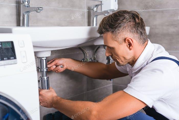 fontanero adulto fijación fregadero en el baño