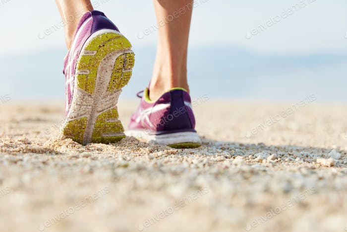 Cropped shot of female`s legs in purple training shoes stands at sandy beach on coastline, being in