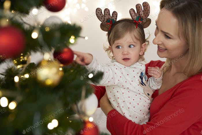 Charming baby and mommy decorating Christmas tree