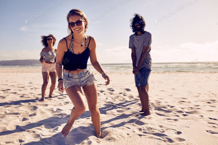 Beautiful woman enjoying on the beach with friends