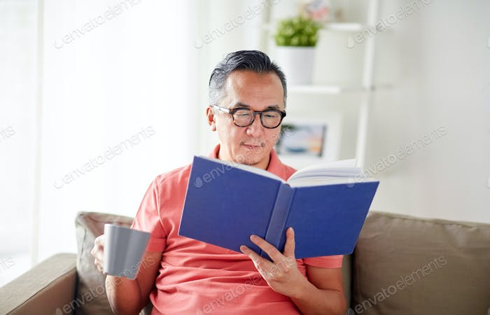 man sitting on sofa and reading book at home