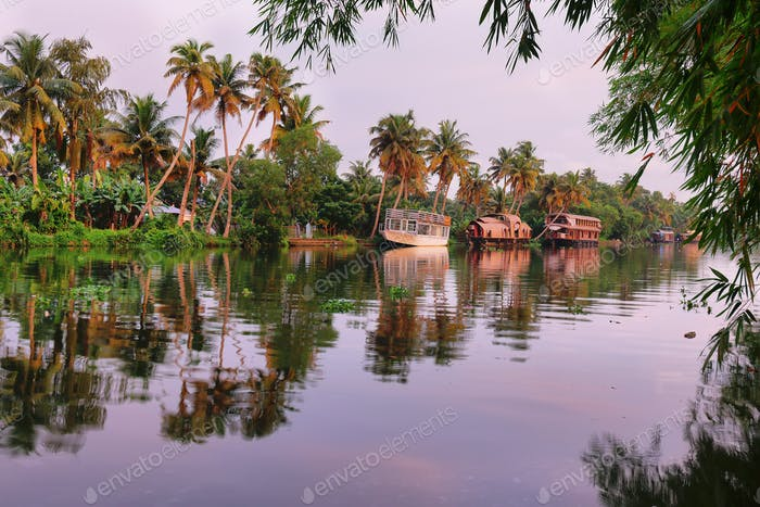Boats on the riverbank of the backwaters in Allepey, Kerala at sunset, India.