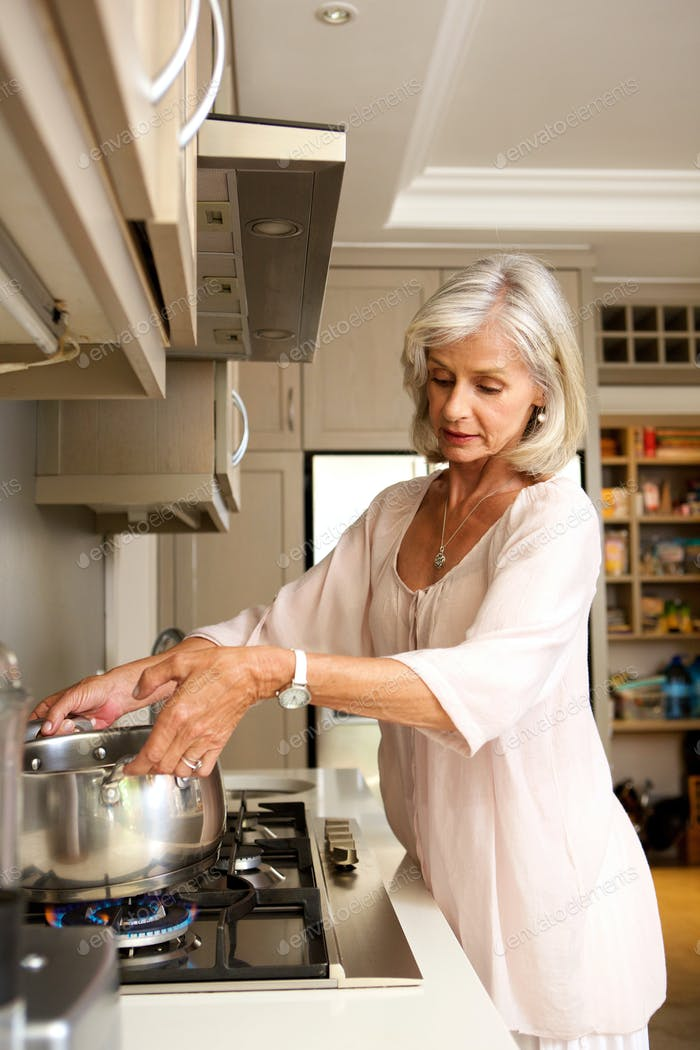 older woman boiling water on kitchen stove top