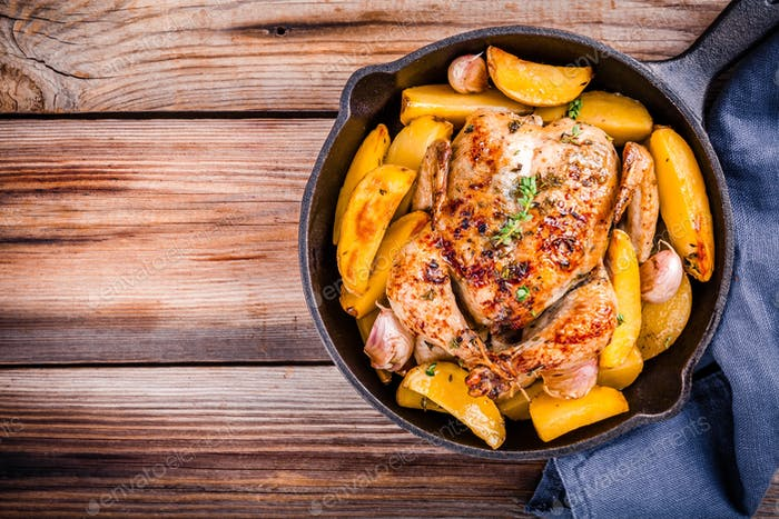 Roasted whole chicken with potatoes and thyme