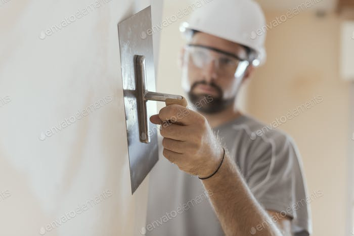 Professional craftsman applying plaster with a trowel