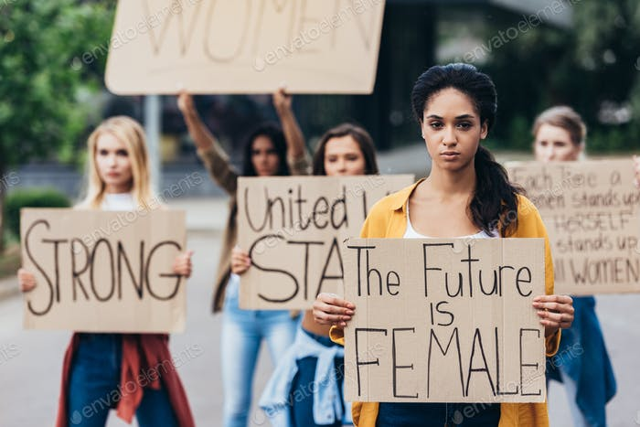 serious african american feminist holding placard with inscription the future is female near women