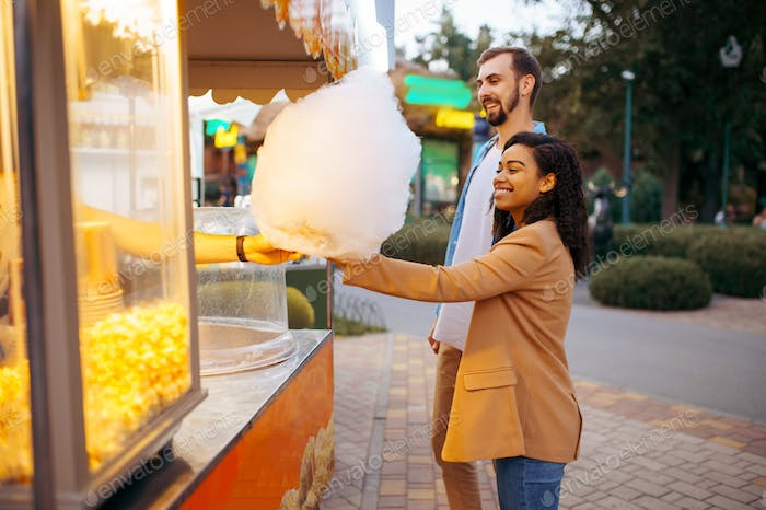 Love couple with cotton candy in amusement park