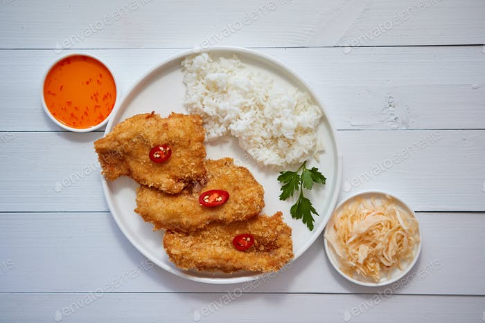 Crispy chicken fried in breadcrumbs served with rice. View from the top on white wooden background
