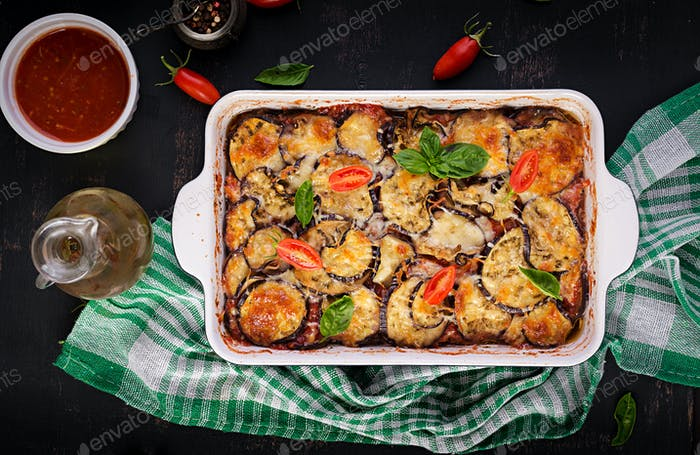 Baked eggplant with cheese on a dark wooden table. Parmigiana melanzane.