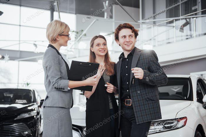 Buying their first car together. High angle view of young car salesman standing at the dealership