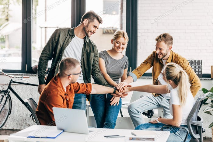 group of smiling young entrepreneurs making team gesture while working on startup together at office