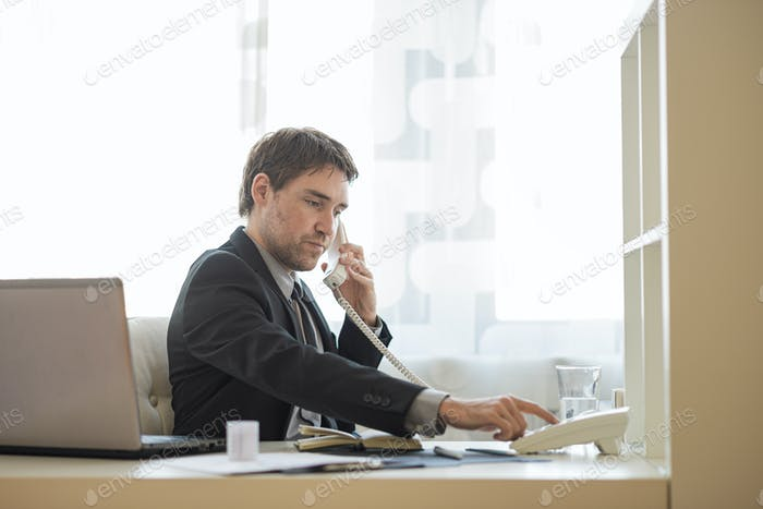 Businessman dialing telephone number sitting at his office desk