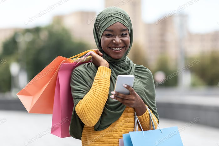 Online Banking. Cheerful Black Muslim Female With Smartphone And Shopping Bags Outdoors